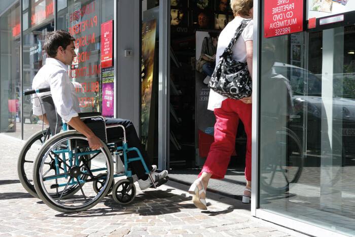 Fauteuil roulant avec handicapé devant vitrine