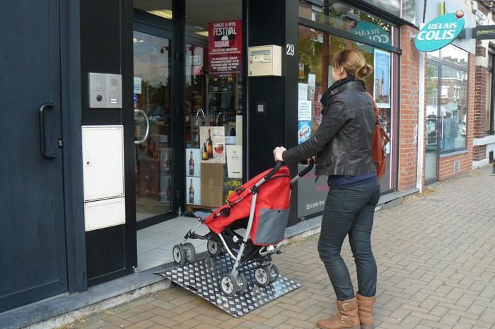 maman poussant une poussette sur rampe d'accès devant magasin